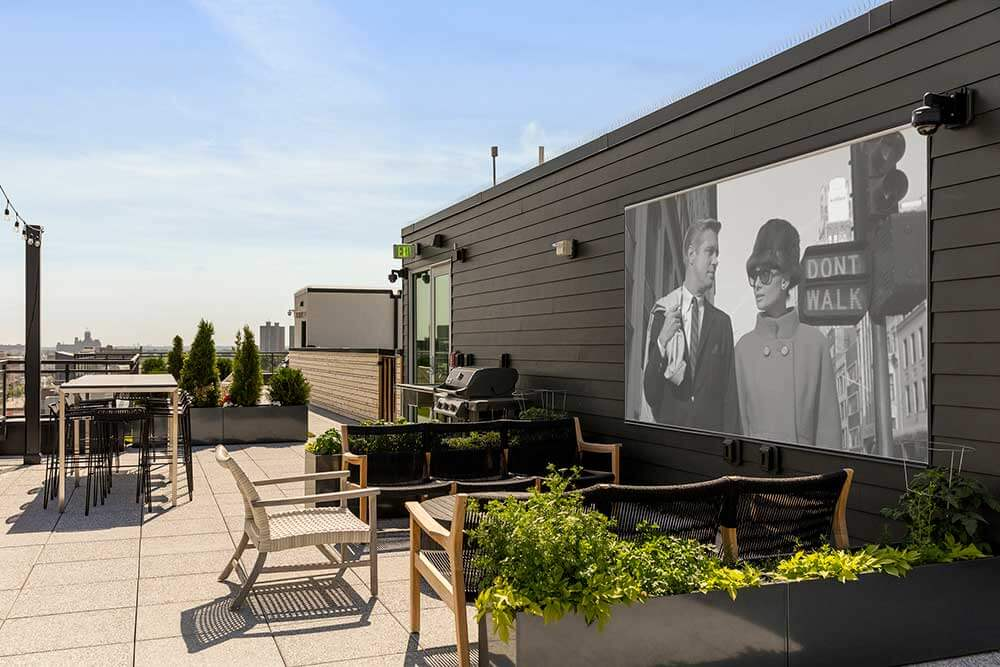 Photo of rooftop entertainment space showing movie screen and seating area