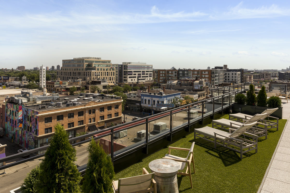 Rooftop entertainment area chaise seating with beautiful views of Uptown neighborhood