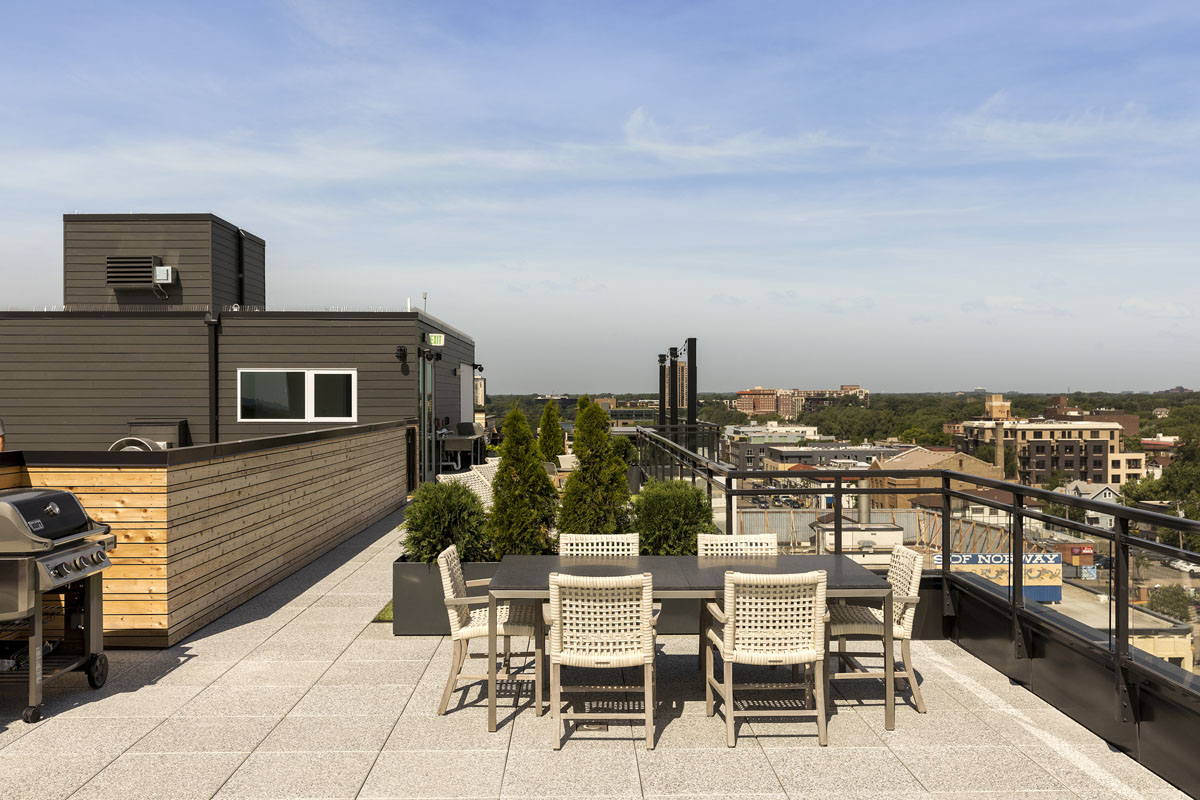 Rooftop entertainment area with seating and gas grill