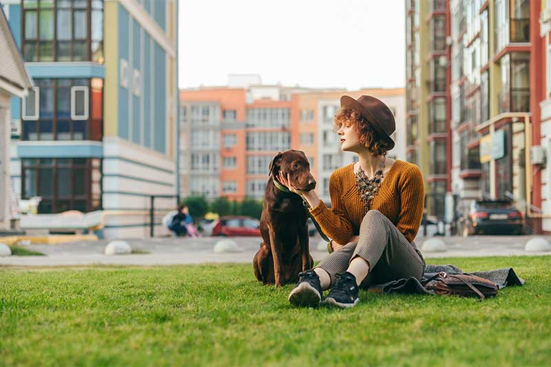 Photo of a woman and her dog in an urban greenspace setting