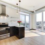 View of open concept kitchen, floor-to-ceiling windows and balcony door