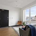 View of studio apartment with modern decor, floor to ceiling windows and efficient use of space