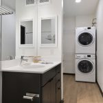 View of bathroom leading into walk-in closet showing stacked washer-dryer