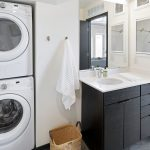 View of bathroom showing stacked washer-dryer
